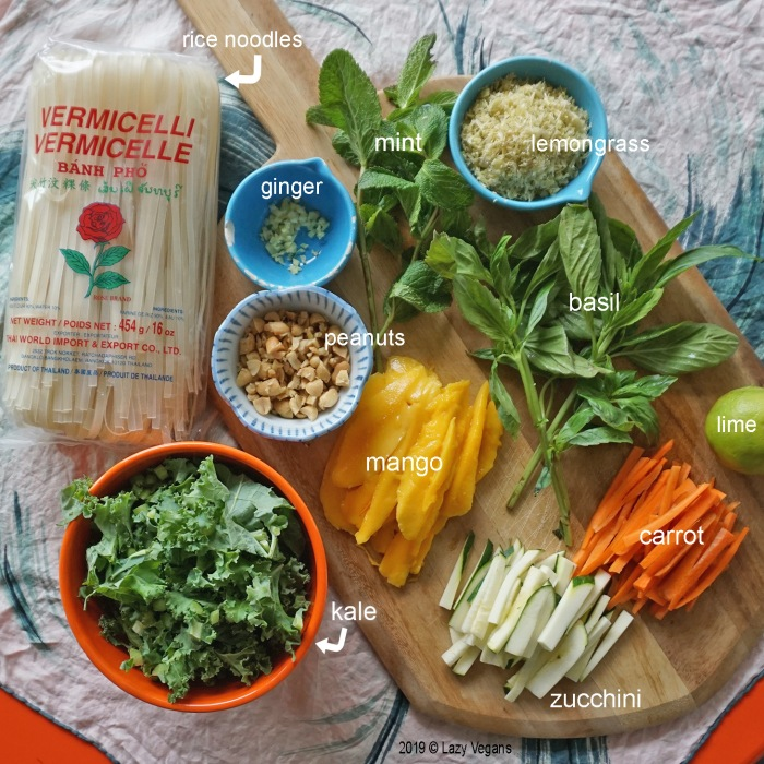 Spring roll bowl ingredients: rice noodles, ginger, peanuts, mint, basil, lemongrass, lime, carrot, zucchini, mango and kale