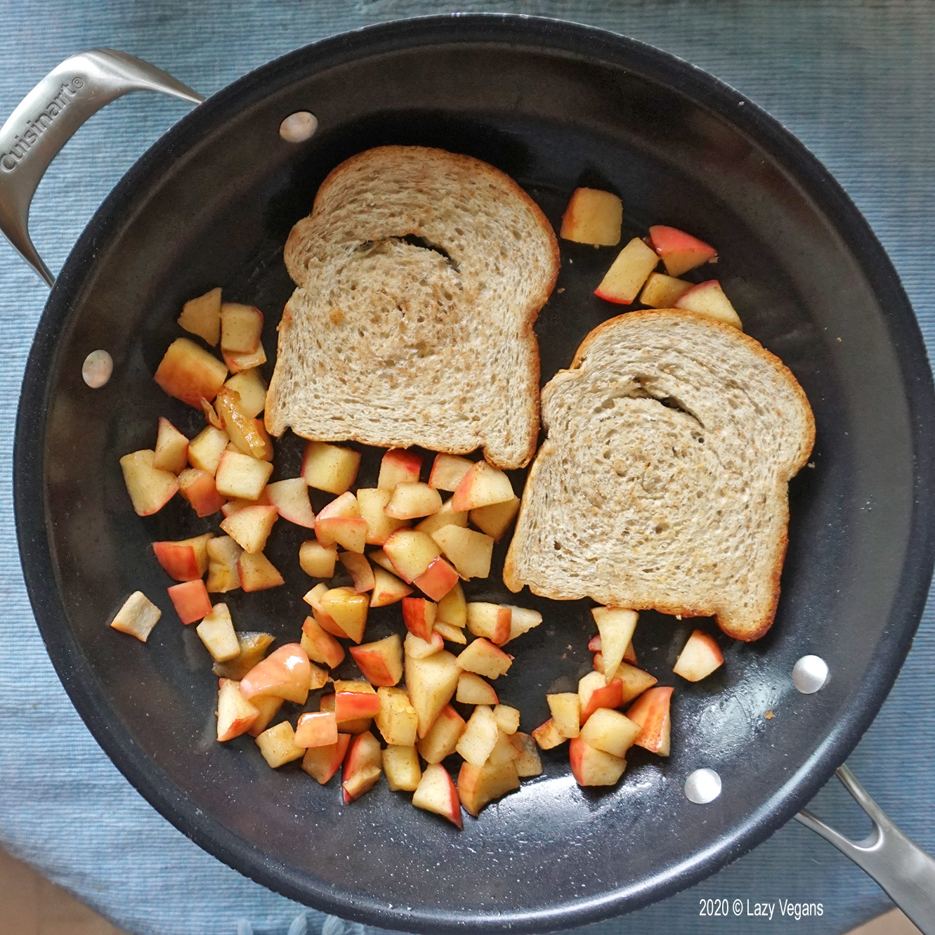 frying apple pieces and two pieces of bread in a pan